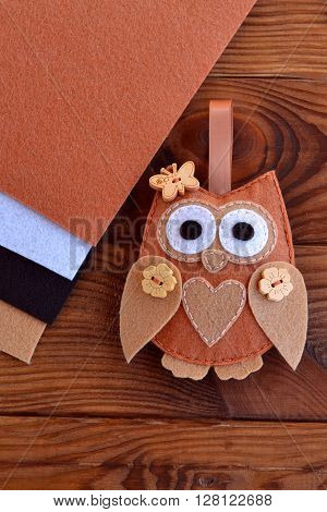 Felt brown owl. Shabby chic style. Kids crafts. Felt sheets. Brown wooden table. Close-up