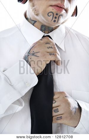 Caucasian mid-adult man with tattoos and piercings adjusting necktie.