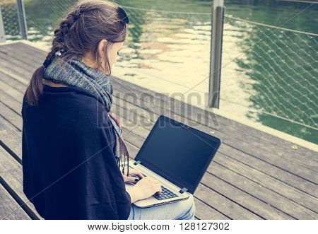 Young woman using laptop at a riverbank. Milleanial working in a park.