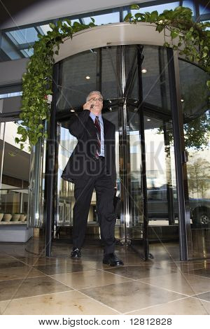 Prime adult Caucasian man in suit walking through revolving door talking on cellphone.