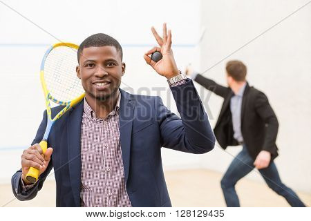 Happy black businessmanholding ball and expressing positive emotions on squash court while his business partner playing squash behind him.