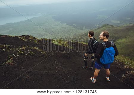 2 Men walk along the hill with backpacks and with white clouds and peak of volcano on background