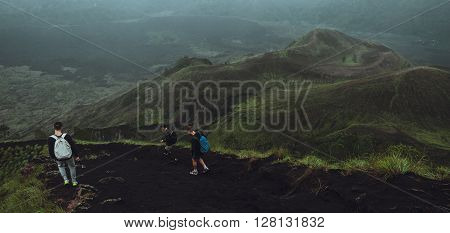 3 Men walk along the hill with backpacks and with white clouds and peak of volcano on background