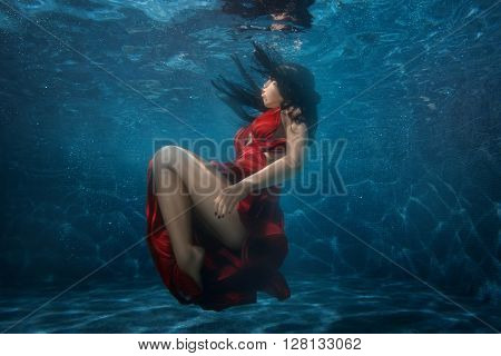 Woman goes to the bottom at the depth of the pool.