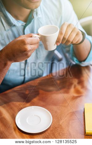 Close up of male arms holding a cup of coffee. The man is sitting at table in cafeteria
