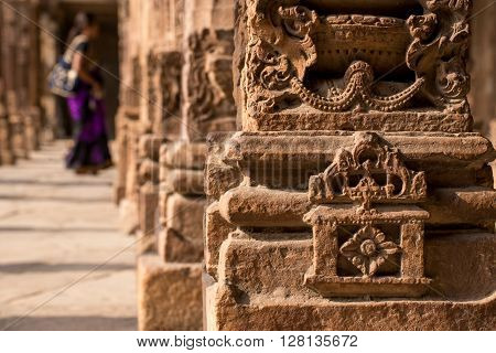 Close-up detail of detail on pillar in an Indian palace woman walking in background. Indo-islamic architecture.