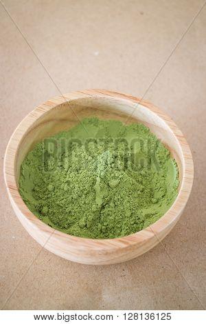 Premium green tea powder in wooden bowl, stock photo