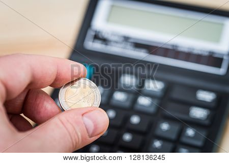 two euro coin in the man's hand - a calculator in the background ** Note: Visible grain at 100%, best at smaller sizes