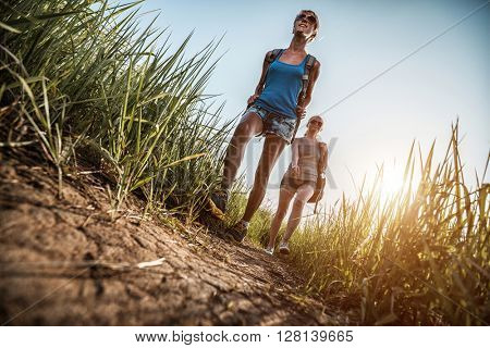 Two athletic young lady walking along the path and the sun is shining