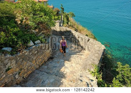 woman going downstairs on the emerald sea 0f Ulcinj Stari Grad, Montenegro