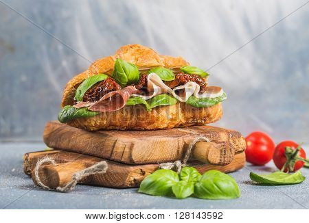 Croissant sandwich with smoked meat Prosciutto di Parma, sun dried tomatoes, fresh spinach and basil on stone textured grey background, selected focus, closeup