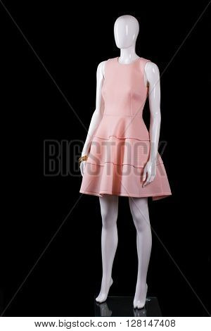 Sleeveless salmon dress with folds. Salmon dress on white mannequin. Stylish mannequin on black background. Trendy garment with golden accessory.