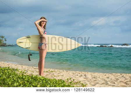 Surfer girl standing with the surf board on the beach looking at camera