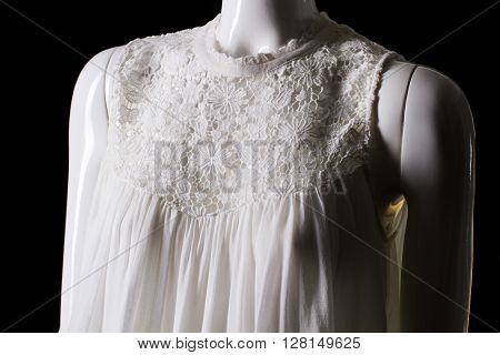 White top with lace insert. Female mannequin wearing white top. Woman's top of stylish design. Low prices for summer clothing.