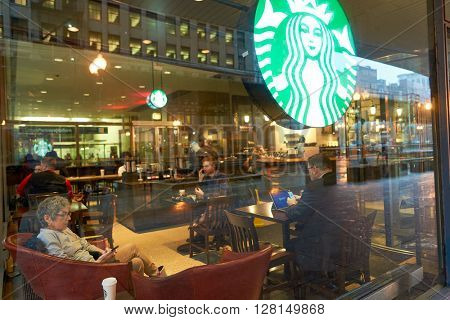 CHICAGO, IL - CIRCA MARCH, 2016: people in Starbucks Cafe. Starbucks Corporation is an American global coffee company and coffeehouse chain based in Seattle, Washington