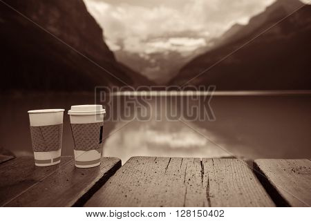 Lake Louise with coffee cup at sunrise in Banff national park with mountains and forest in Canada.