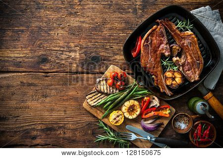 Roasted lamb meat with vegetables on grill pan on wooden background