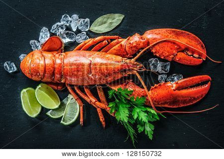 Top view of whole red lobster with ice and lime on a black slate plate