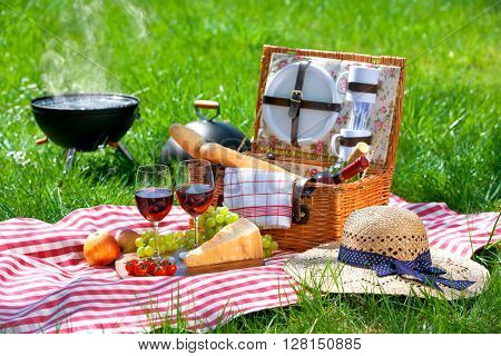 Picnic setting with red wine glasses, picnic hamper basket and burning fire in a portable barbecue