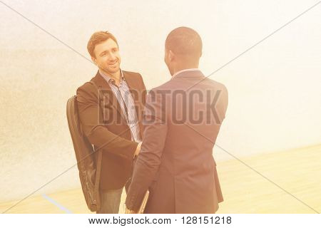 Picture of two businessmen before having match in squash. Happy men in business suits shaking hands on squash court.