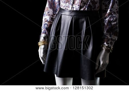 Black skirt, watch and bracelet. Skirt with folds on mannequin. Girl's high-quality leather skirt. Brand new designer clothes.