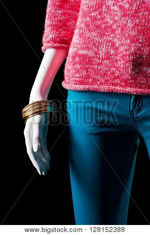 Pink sweater, pants and bracelets. Female mannequin's hand with bracelets. High-quality accessory on sale. Final discount at boutique.