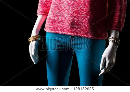 Pink pullover, watch and bracelet. Mannequin wearing pullover and accessories. Lady's warm garment for spring. Classic watch and gold bracelet.