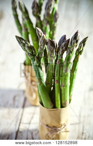 two bunches of fresh asparagus closeup on wooden table