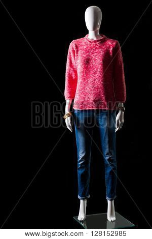 Pink sweater and blue jeans. Mannequin wearing jeans with sweater. Girl's bright spring apparel. Quality clothing of simple design.