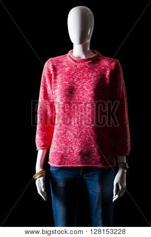Pink pullover with blue jeans. Jeans and pullover on mannequin. Woman's bright outfit for spring. Warm colors and simple pattern.
