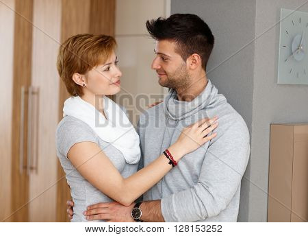 Young loving couple embracing at home, smiling.