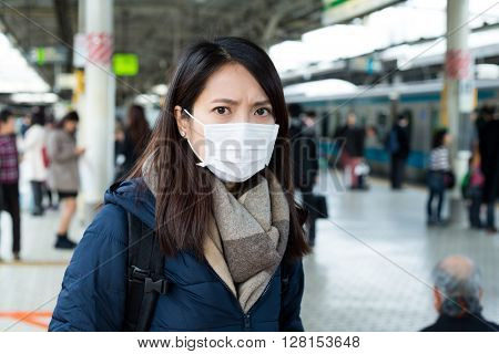 Woman with face mask protection in train platform