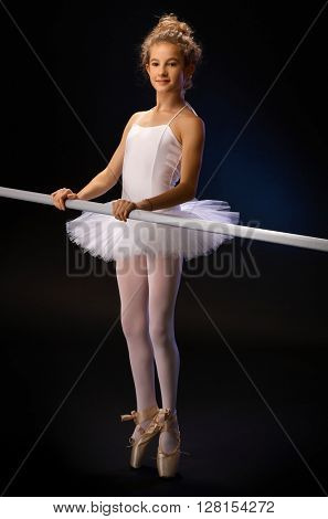 Ballet student practicing by ballet bar, standing on her toes. Full size over black background.