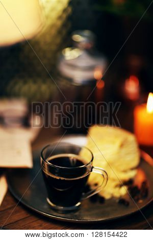 Glass cup of coffee with cake on dark table