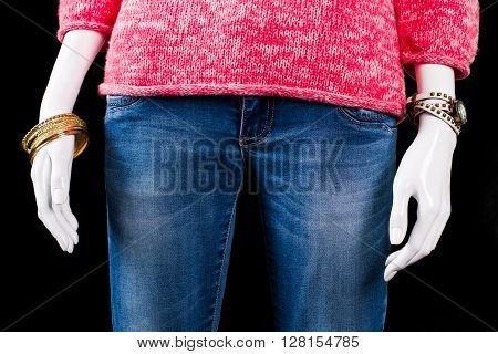Jeans with bracelet and watch. Accessories and jeans on mannequin. Lady's casual jeans with pullover. Bright apparel on black background.