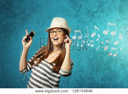 Young woman in earphones listening to music against musical background with notes