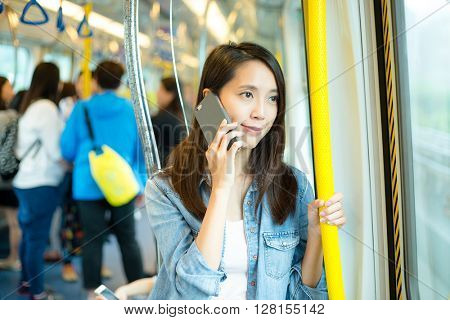 Woman pick up a call inside train compartment
