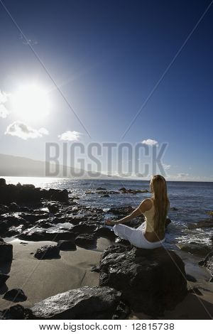 Young adult Asian Filipino female meditating on rocky beach in Maui Hawaii.