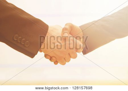 Two business partners shaking hands indoors. People having deal in signing agreement or contract betweent two companies.
