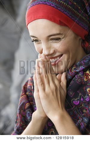 Caucasian young adult woman with hands together in prayer position holding up to face and smiling.
