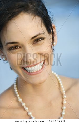 Portait of Caucasian mid-adult woman in pearls smiling and looking at viewer.