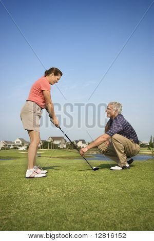 Caucasion mid-adult woman holding golf club while mid-adult man kneels holding club teaching.