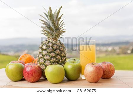 glass of orange juice and lots of fruits on wooden table outdoor