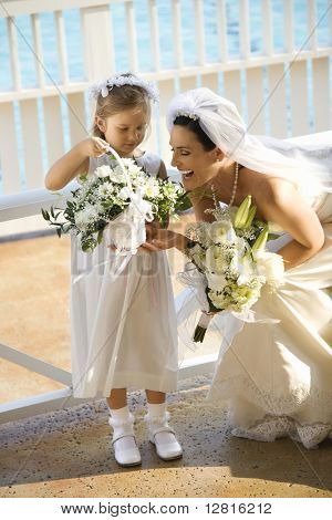 Caucasian mid-adult bride kneeling next to flower girl admiring her flowers.