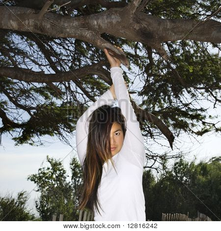 Young adult Asian female hanging from a tree looking at viewer.