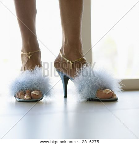 Feet of Caucasion middle-aged woman wearing furry heels and gold chain anklets.