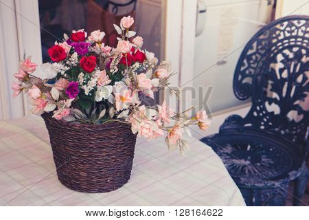 Decoration artificial flower on table ( Filtered image processed vintage effect. )