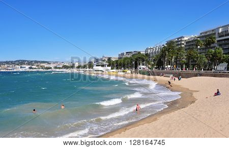 CANNES, FRANCE - MAY 15: Sunbathers at the public beach at the end of the Promenade de la Croisette on May 15, 2015 in Cannes, France. This promenade is famous because of the Cannes Film Festival