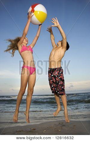 Kaukasische pre-teen meisje en jongen spelen met beachball op het strand.