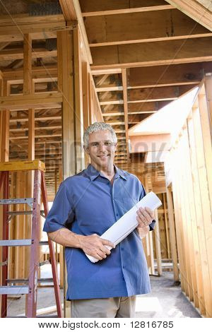 Caucasian mid-adult male holding blueprints in building construction site.
